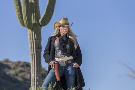 Ein blondes Modell posiert als Cowgirl in einer westlichen Umgebung Standard-Bild - 77619338