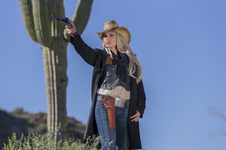 Ein blondes Modell posiert als Cowgirl in einer westlichen Umgebung Standard-Bild - 77691604