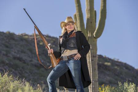 Un modelo rubio posando como una vaquera en un ambiente occidental Foto de archivo