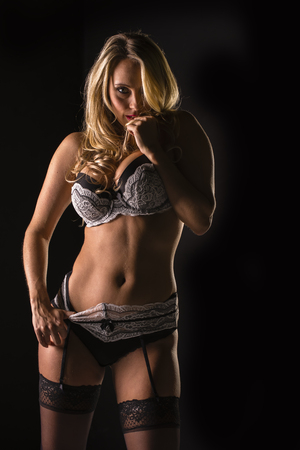A blonde model poses in lingerie in a studio environment photo