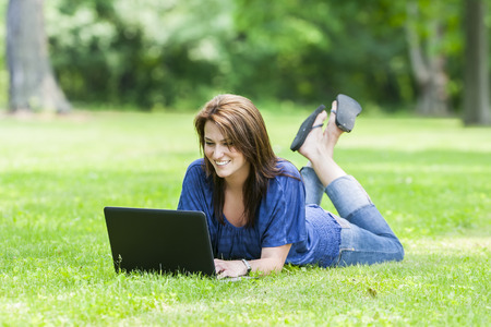 woman on phone: A beautiful brunette model working on a computer and talking on a mobile phone in an outdoor environment