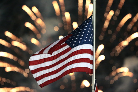The Stars and Stripes wave through the night sky with fireworks in the background Editorial