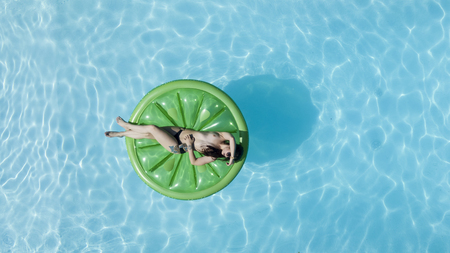 A model poses topless in a swimming pool environment. Stock Photo