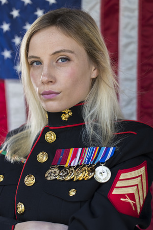 A blonde model posing in military uniform in an outdoor environment