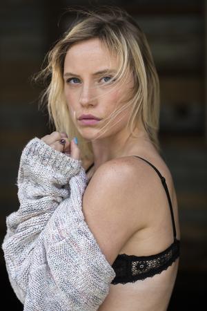 Een blonde lingerie model poseren in een buitenomgeving