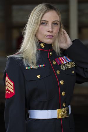 屋外の環境で軍服を着てポーズ金髪モデル 写真素材