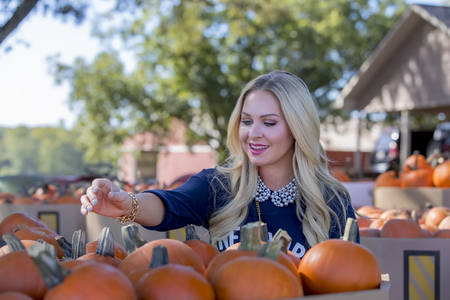 A blonde model shopping for pumpkins for Halloween Stock Photo