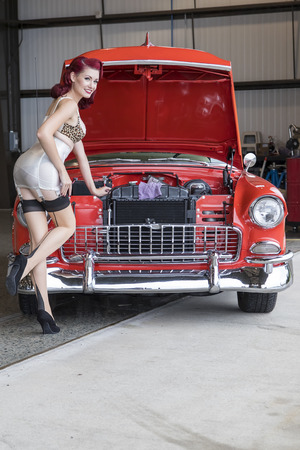 A pinup model posing with a 1950s car