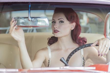 Ein Pinup-Model posiert mit einem 50er Jahre Auto Standard-Bild - 87803118