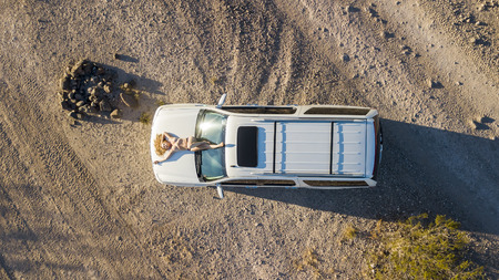 Topless model posing with a vehicle in the desert Stock Photo