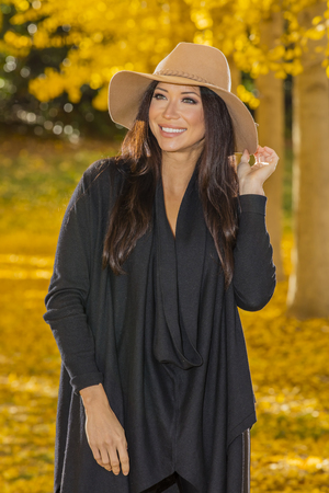 A beautiful ethnic brunette model posing outdoors in a field of yellow leaves. Stock Photo