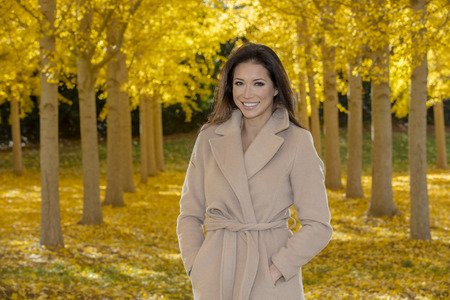 A beautiful ethnic brunette model posing outdoors in a field of yellow leaves. Banco de Imagens