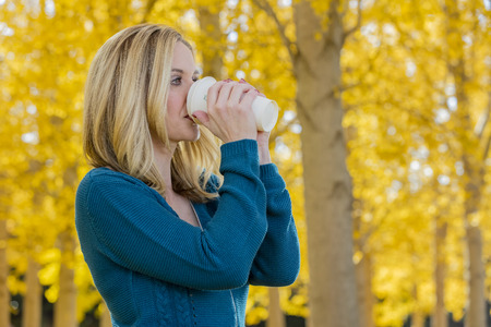 A beautiful blonde model drinking a hot beverage while posing outdoors in a field of yellow leaves.