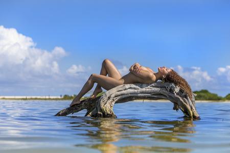 A nude hispanic brunette model enjoying the beach Stock Photo