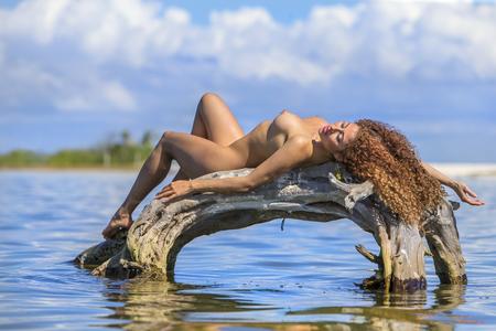 A nude hispanic brunette model enjoying the beach 写真素材