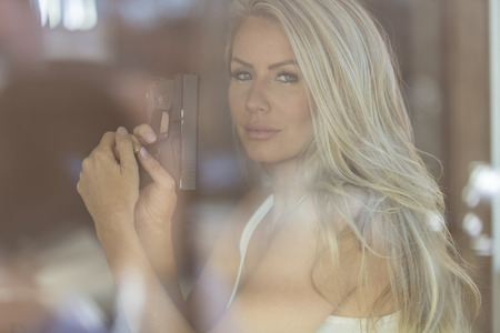 A beautiful blonde model holds a pistol for protection on a sunny day.