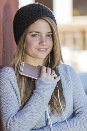 A beautiful young teenage blonde girl listens to her music through her earphones.
