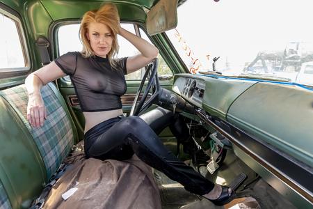 A beautiful implied blonde model posing in a auto salvage yard. Foto de archivo
