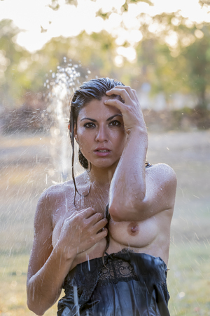 A beautiful hispanic brunette model cooling off on a summer day Stock Photo