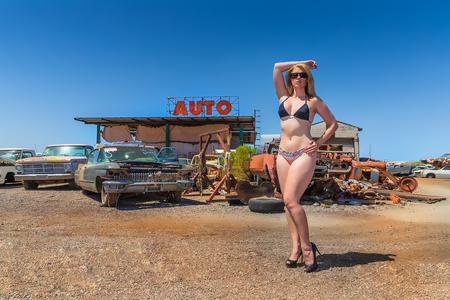 A beautiful blonde bikini model posing in a auto salvage yard. Editorial
