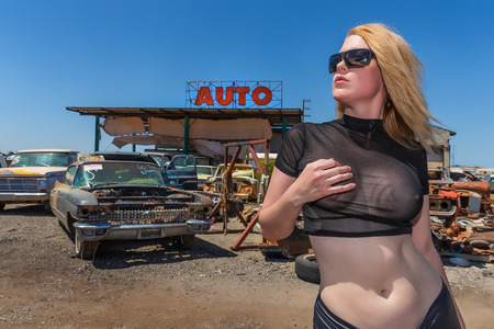 A beautiful implied blonde model posing in a auto salvage yard. Sajtókép