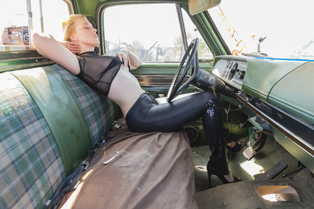 A beautiful implied blonde model posing in a auto salvage yard. Stock fotó