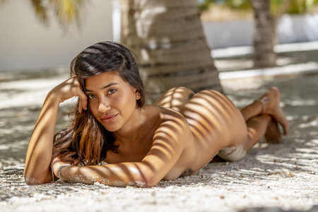 A nude hispanic brunette model poses in an outdoor environment Фото со стока - 102584316