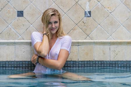 A beautiful blonde bikini model enjoys a day by by the pool