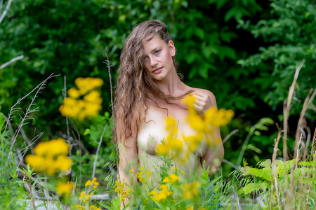 Gorgeous nude blonde model posing in an outdoor environment
