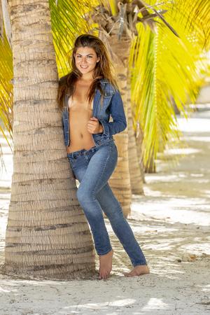 A beautiful hispanic implied nude brunette model posing outdoors on a Caribbean island