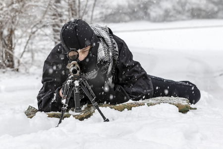 A young military man training to shoot a weapon during a snowstorm in an outdoor environment. Stock Photo