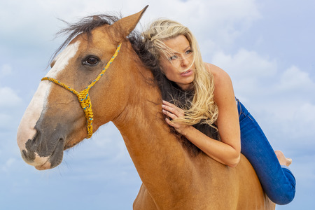 A topless blonde model rides a horse on a Caribbean beach Stock Photo