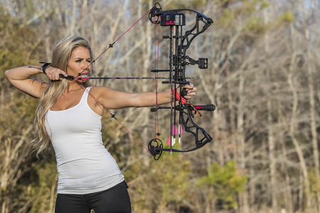 A beautiful blonde model posing with a bow and arrow outdoors Stock Photo