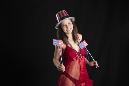 A beautiful brunette model posing in a studio environment holding America items for the 4th Of July celebration Stok Fotoğraf