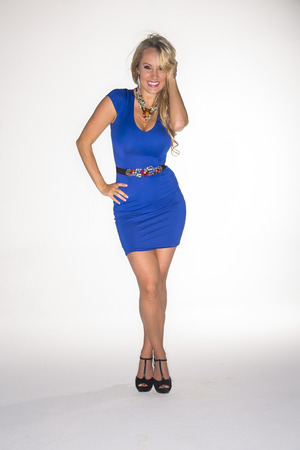 A gorgeous blonde model posing in a dress in a studio environment Stock Photo