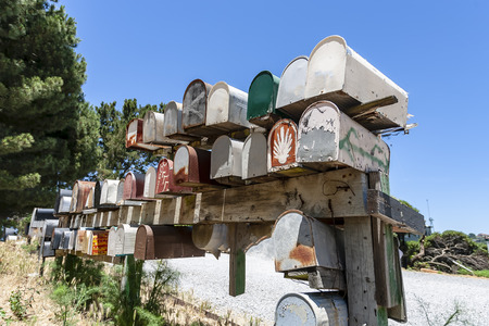 Colorful antique mailboxes sit on a roadside Editorial