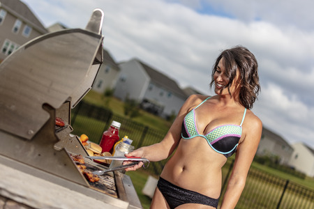 A beautiful brunette model enjoying a day outside while cooking on a grille Stock Photo - 105089608