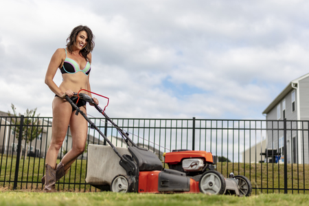 A gorgeous brunette model cutting the grass in a bikini and boots
