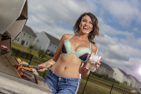 A beautiful brunette model enjoying a day outside while cooking on a grille Stock Photo - 105088909