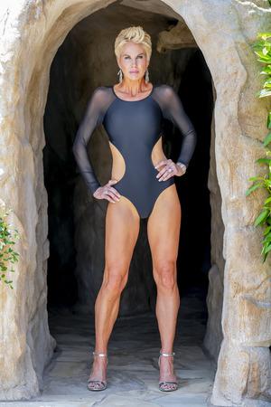 Una hermosa modelo de bikini rubia madura posa al aire libre cerca de una piscina.