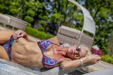 A beautiful mature blonde bikini model poses outdoors near a swimming pool.