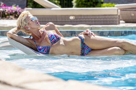 A beautiful mature blonde bikini model poses outdoors near a swimming pool.