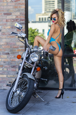 A gorgeous Brazilian Blonde bikini model poses with a motorcycle on the city streets Imagens - 105955449