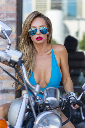 A gorgeous Brazilian Blonde bikini model poses with a motorcycle on the city streets
