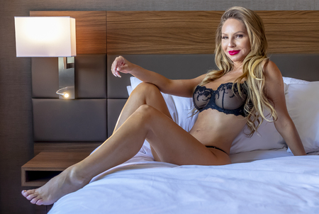 A beautiful Brazilian blonde lingerie model relaxing in a home environment Stock Photo