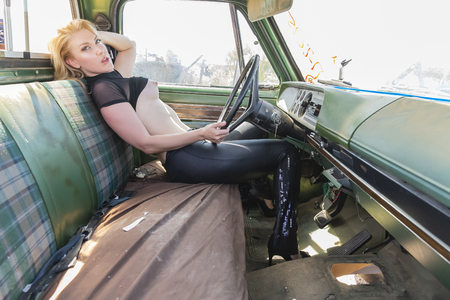 A beautiful implied blonde model posing in a auto salvage yard. Standard-Bild