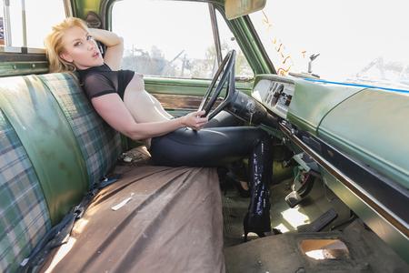 Una bellissima modella bionda implicita in posa in un cantiere di salvataggio di auto.