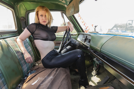 A beautiful implied blonde model posing in a auto salvage yard. Reklamní fotografie