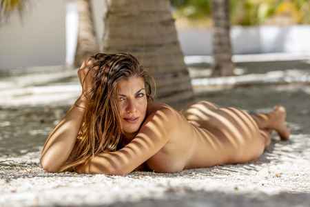 A nude hispanic brunette model poses in an outdoor environment
