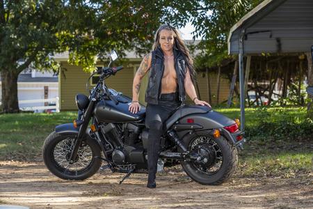 Una hermosa modelo rubia posa con una motocicleta callejera en un día soleado